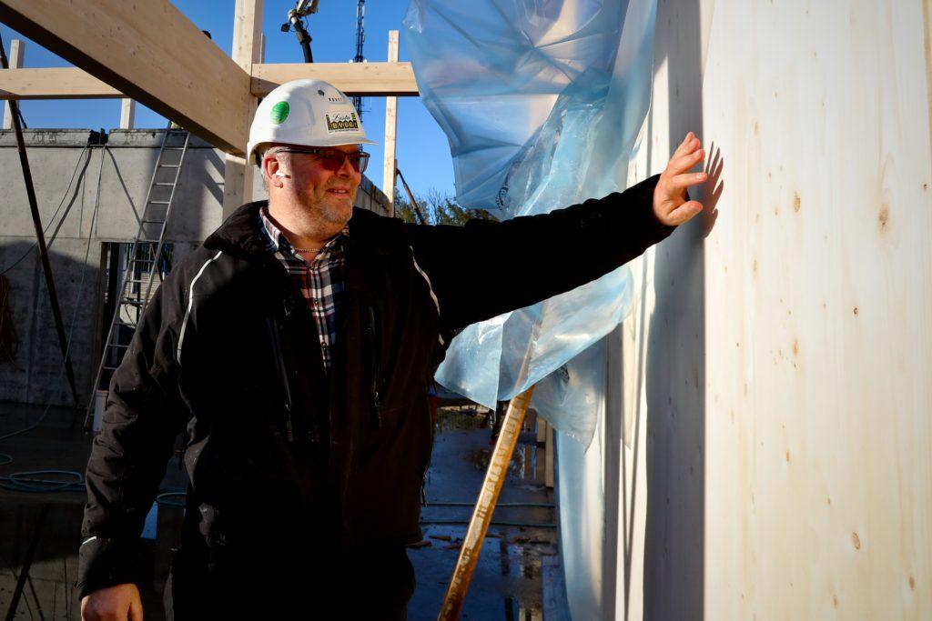 Daglig leder i Lista Bygg, Jan Richard Johannessen, viser frem en av flere massivtrevegger som vil pryde klasserommene.